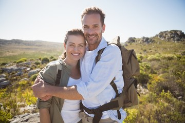Hiking couple embracing and smiling at camera