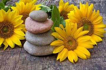 Acrylic Prints Steinturm auf Holz mit Sonnenblumen, Textfreiraum