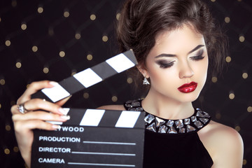 Fashion woman with sexy red lips holding cinema clap. Super star