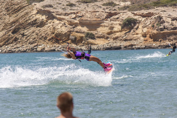a young girl engaged in an acrobatic leap to kitesurf
