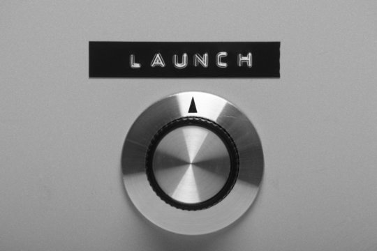 Control switch on a panel pointing at the word Launch