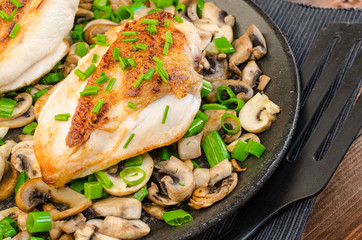 Chicken breast with mushrooms and spring onions on pan