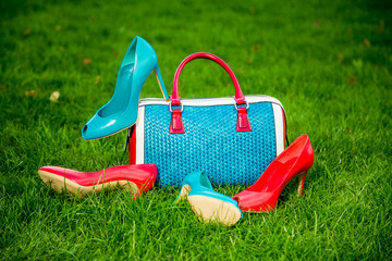 Fotobehang two pairs of green and red shoes and bag lay on the grass