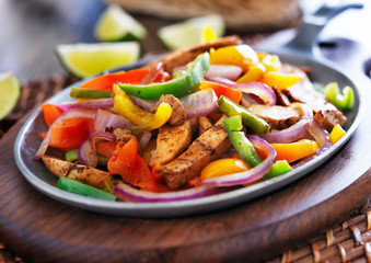 Wall Mural - mexican chicken fajitas in iron skillet with peppers