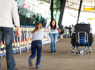 young girl running to her mother at airport