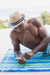Handsome shirtless man listening to music poolside