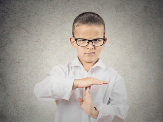 Boy showing time out gesture with hands, grey wall background