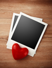 Two photo frames and red candy heart on wooden background