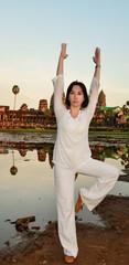 portrait of elegant mature woman doing yoga outdoors