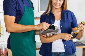 Worker Swiping Credit Card With Woman Holding Screwdriver Set