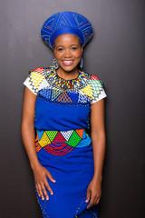 african zulu woman standing against black wall