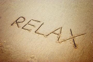 relax handwritten inscription in sand on a beach
