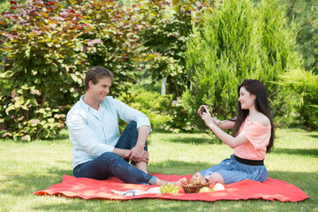 Happy romantic couple taking pictures at picnic