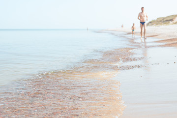Baltic sea shore, father and son running together