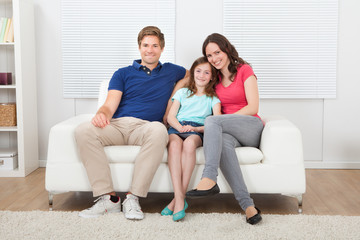 Family Sitting On Sofa At Home