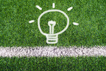 Idea light bulb hand drawing on soccer field grass