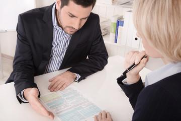 Besprechung im Büro: Ausfüllen Formular Beurteilung Mitarbeiter