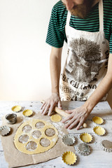 bearded young man with apron making shortcrust pastry