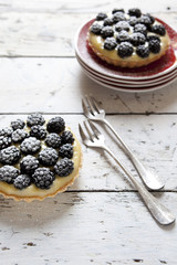 two blackberries tart with pastry cream on wooden table
