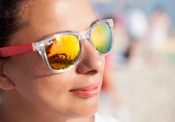 Smiling beautiful woman on a beach with sunglasses