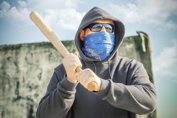 Man with a baseball bat at outdoor near wall