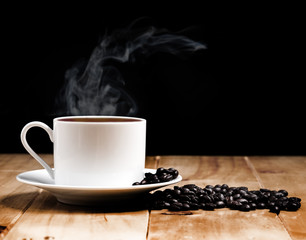 White coffee cup on wooden table and dark background
