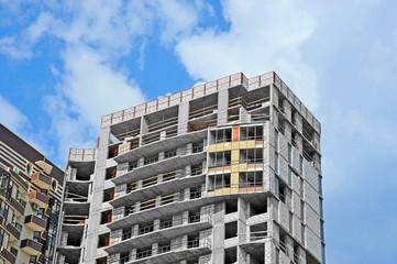 Building construction site wok with balcony against blue sky
