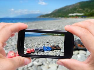 Hands taking photo flip flops with smartphone