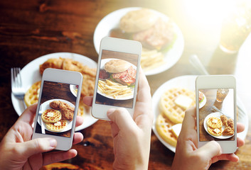 friends using smartphones to take photos of food
