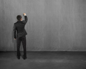 businessman standing and drawing on wall