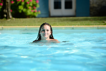cheerful young woman in resort swimming pool summer vacations