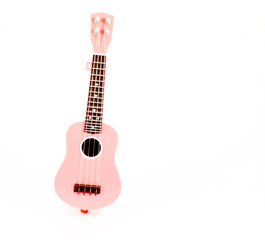 pink guitar toy isolated on white background