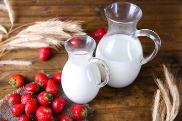 Ripe sweet strawberries and jug with milk