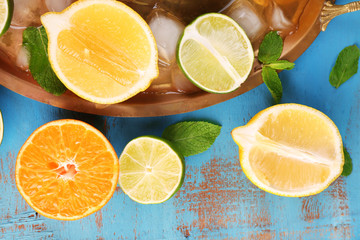 Different sliced juicy citrus fruits with ice