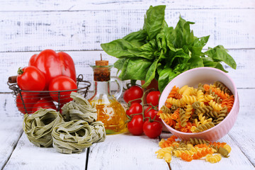 Composition of colorful pasta, fresh tomatoes, basil, olive oil