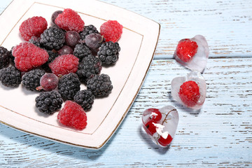 Ice cubes with red currant and frozen forest berries