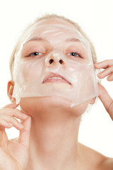 Girl woman in facial peel off mask. Skin care.