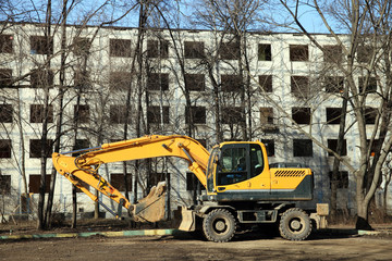 The yellow excavator against empty building