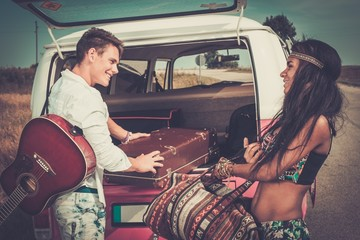 Multi-ethnic hippie couple packing luggage
