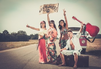 Multi-ethnic hippie hitchhikers on a road
