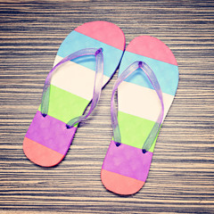 Summer flip flops on wood background