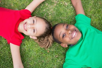 Cute children smiling at camera outside on the grass