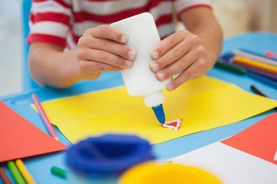 Cute little boy making art in classroom