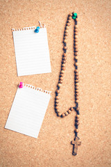 rosary beads on cork board