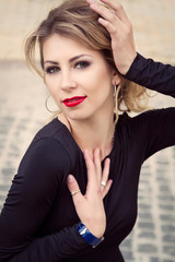 Portrait of blonde woman with red lips and black dress