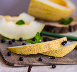 fresh melon and blueberries on a wooden cutting board. selective