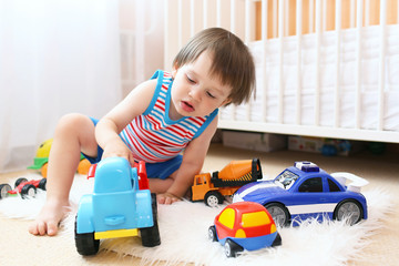 little boy playing cars at home