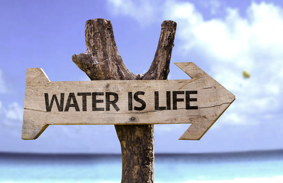 Water is Life wooden sign with a beach on background