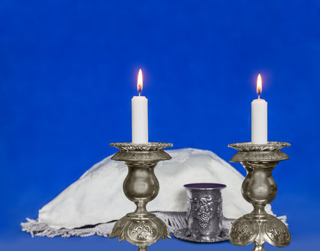 Sabbath candles, covered challah, blue soft texture background