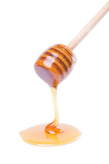 Honey dripping from wooden dipper